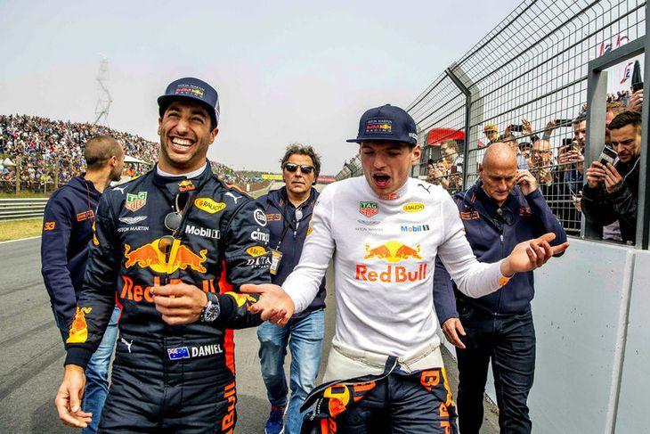 Daniel Ricciardo (t.v.) með vörumerki sitt á lofti, skælbrosið, eftir að liðsfélagi hans Max Verstappen ...