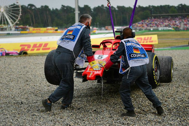Brautarverðir aðstoða dráttarvél við að flytja Ferrarifák Sebastian Vettel af vettvangi í Hockenheim.