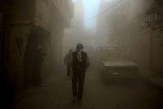 Fólk á gangi í Douma, en mikill reykur og ryk er í lofti eftir loftárásir ...